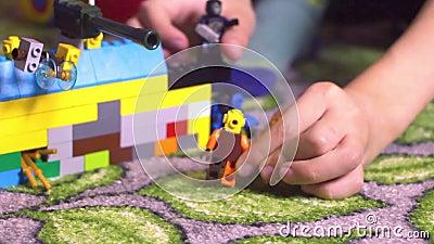 玩具和使用有blondi头发开会的小孩儿童小男孩围拢的与积木lego人形象 股票视频