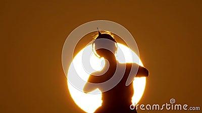 现出轮廓女孩东方舞蹈家在日落的一个舞蹈 影视素材