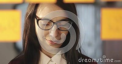 玻璃的可爱的女商人在贴纸在玻璃写信息并且胶合在办公室 股票视频