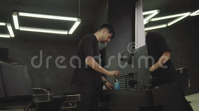理发师在理发店消毒有浪花的一把电剃刀并且清洗与一把刷子 手扶的射击 4K 股票录像
