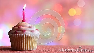 生日杯形蛋糕和蜡烛在五颜六色的defocused背景党概念 股票视频
