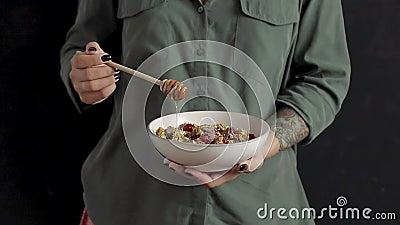 用干果和巧克力将蜂蜜浇在燕麦上 股票视频