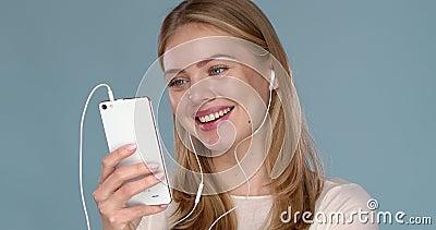 用电话耳机在蓝墙上隔离地摆姿势听音乐的幸福美女 股票录像