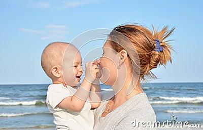 男孩和他的在海滩的母亲乐趣