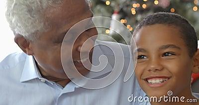 男孩慢动作序列坐有父亲和祖父的沙发在圣诞节时间