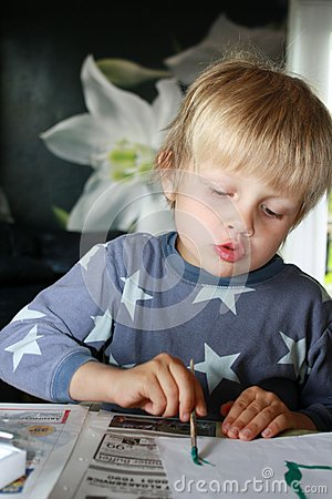 男孩集中的绘画