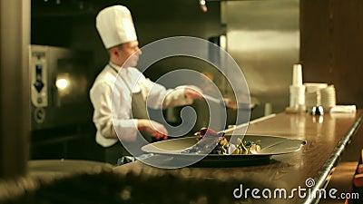男性厨师在餐馆厨房里烹调Flambe