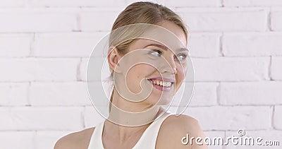 白砖墙背景上微笑的白人美女特写 股票录像