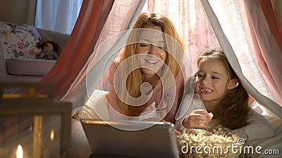 的女孩和享用她的妈妈观看动画片在网上在帐篷在托儿所 股票视频