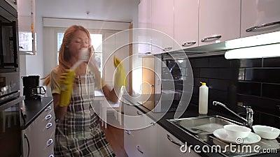 洗盘子和跳舞在厨房里的愉快的主妇 慢的行动 影视素材