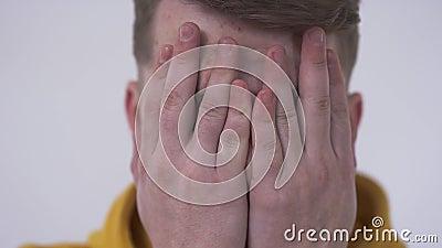 看照相机从后面手指的一害羞的年轻人的特写镜头盖面孔用他的手 掩藏的概念 股票视频