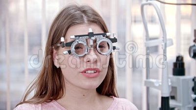 眼科治疗 — 一位坐在视力测试仪中的微笑年轻女性 — 阅读某些东西 股票视频