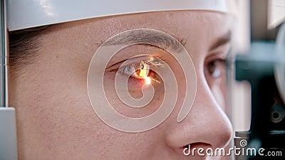 眼科治疗 — 一名年轻女性用特殊大的不同颜色的光来检查视力 影视素材