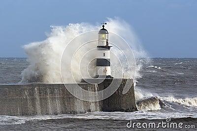 碰撞在Seaham灯塔的波浪