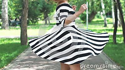 礼服的女孩通过夏天公园和旋转愉快地走 一个女孩的画象夏天礼服的和 影视素材