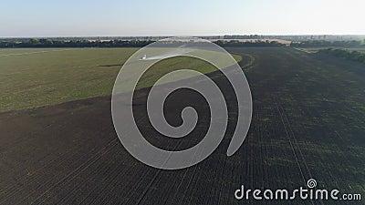 种田,双翼飞机飞行在领域用麦子和飞溅化学制品反对葡萄酒俯视图的虫  股票录像