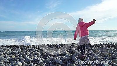 穿桃红色夹克的逗人喜爱的小女孩使用与波浪由海在冷的春日 股票录像