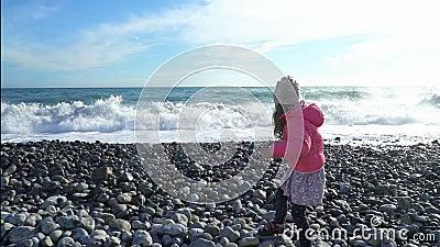 穿桃红色夹克的逗人喜爱的小女孩使用与波浪由海在冷的春日 股票视频
