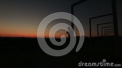 站立在红色日落的高科技桥梁的孤独的体贴的妇女剪影  股票录像