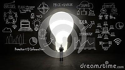 站立在黑色,电灯泡光、经营计划和各种各样的图表形状前面的商人在黑墙壁