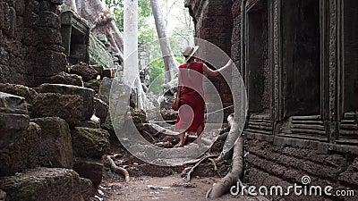 红色礼服的白种人妇女在塔布茏寺中废墟走 影视素材