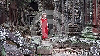 红色礼服的白种人妇女在塔布茏寺中废墟走 股票录像