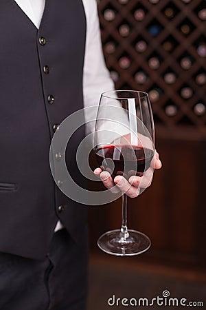 纯熟男性侍者运载一个葡萄酒杯图片