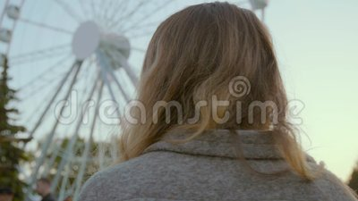 美丽的女孩沿一件时髦的淡色外套的吸引力公园走 股票视频