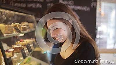 美丽的女性顾客购物陈列室在指向她买的点心的面包店商店 股票录像