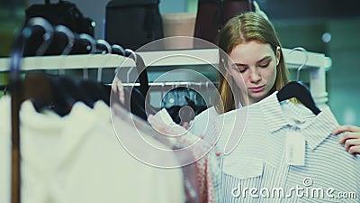 美女在挂衣架的购物衣裳在精品店 股票视频