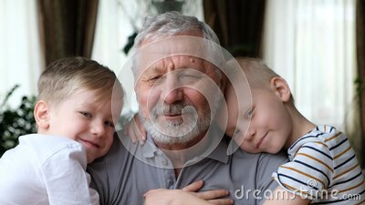 老爷爷,孙子们看着镜头,微笑拥抱 股票录像