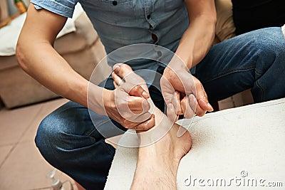 做繁体中文脚按摩的男按摩师对成人腿和脚.
