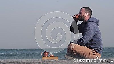 蓄着胡须的白人在海边的码头喝中国茶 风扫沙,海鸥在背景中飞翔 股票录像