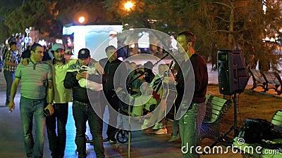街道艺术家弹吉他并且唱歌曲入在雅尔塔堤防,克里米亚的话筒 影视素材