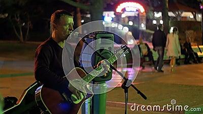 街道艺术家弹吉他并且唱歌曲入在雅尔塔堤防,克里米亚的话筒 股票录像
