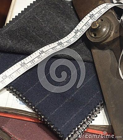 裁缝剪刀,衣服布料,卷尺和书的汇集一起.
