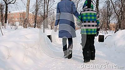 走在冬天城市公园的妈妈和儿子 回到视图 股票录像