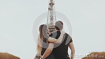 走在埃佛尔铁塔附近的年轻愉快的夫妇在巴黎,法国 男人和妇女神色和纪念碑和上升手 股票录像