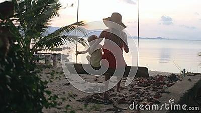 赶走在海滩的摇摆的孩子和母亲 股票录像