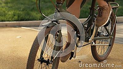 赶走自行车车轮 关闭少妇自行车骑马在路公园 股票录像