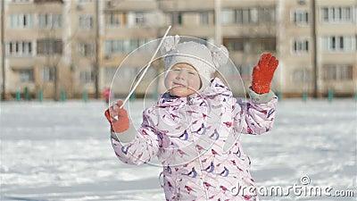 跑户外在多雪的体育场的微笑的小女孩在学校附近 股票录像
