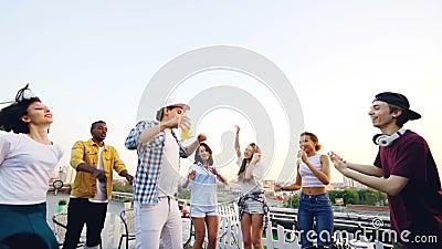 跳舞在屋顶的可爱的年轻人和妇女的慢动作放松和获得与使用的节目播音员的乐趣笑和 股票视频