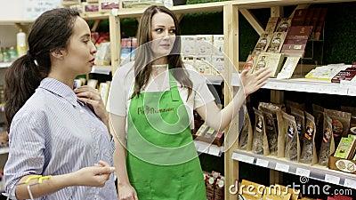身穿绿色围裙的友好店员向有吸引力的女性顾客展示一些商品,并提供信息 影视素材