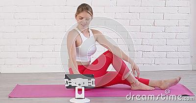 运动员女性坐在客厅的瑜伽垫上,在平板电脑上浏览和观看 股票录像