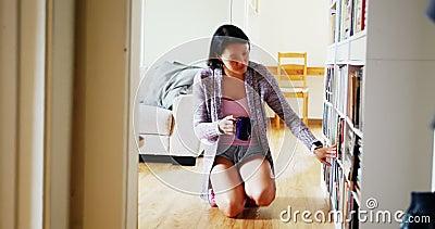 选择书的妇女从书架在客厅 股票录像