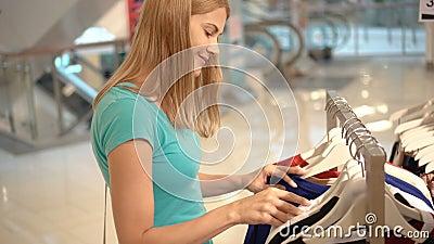 选择衣裳的年轻可爱的妇女在商店 购物在购物中心,销售时间 消费者至上主义概念 股票录像