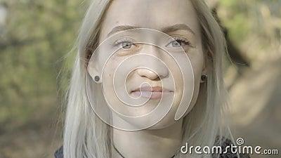 金发女性脱下面罩,对着镜头微笑的极致特写 白种女孩肖像 股票录像