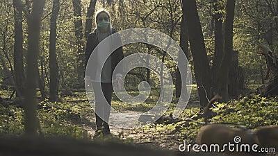 金发白人女孩戴面罩戴墨镜在公园散步,年轻女子与狗一起散步 股票录像