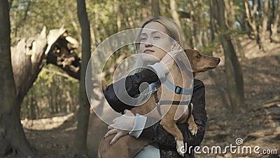 金色榛子笑脸的女人,手抱着小棕色宠物,脱掉面罩 快乐的高加索人画像 股票录像