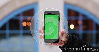雪落在拿着有绿色屏幕的人` s手智能手机在他的胳膊 股票录像